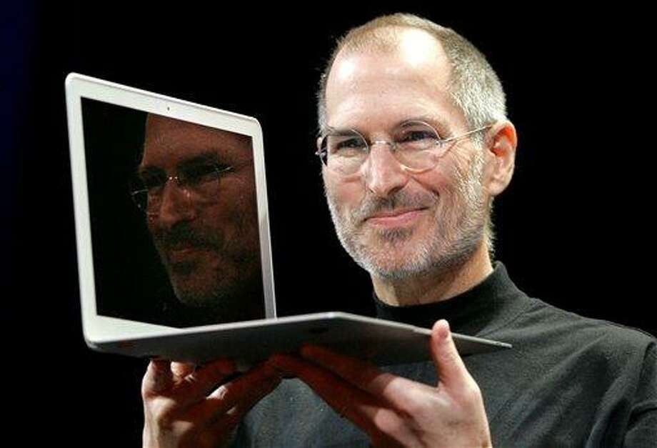 FILE - In this Jan. 15, 2008, file photo, Apple CEO Steve Jobs holds up the new MacBook Air after giving the keynote address at the Apple MacWorld Conference in San Francisco. Apple on Wednesday, Oct. 5, 2011 said Jobs has died. He was 56. (AP Photo/Jeff Chiu, File) Photo: ASSOCIATED PRESS / AP2008