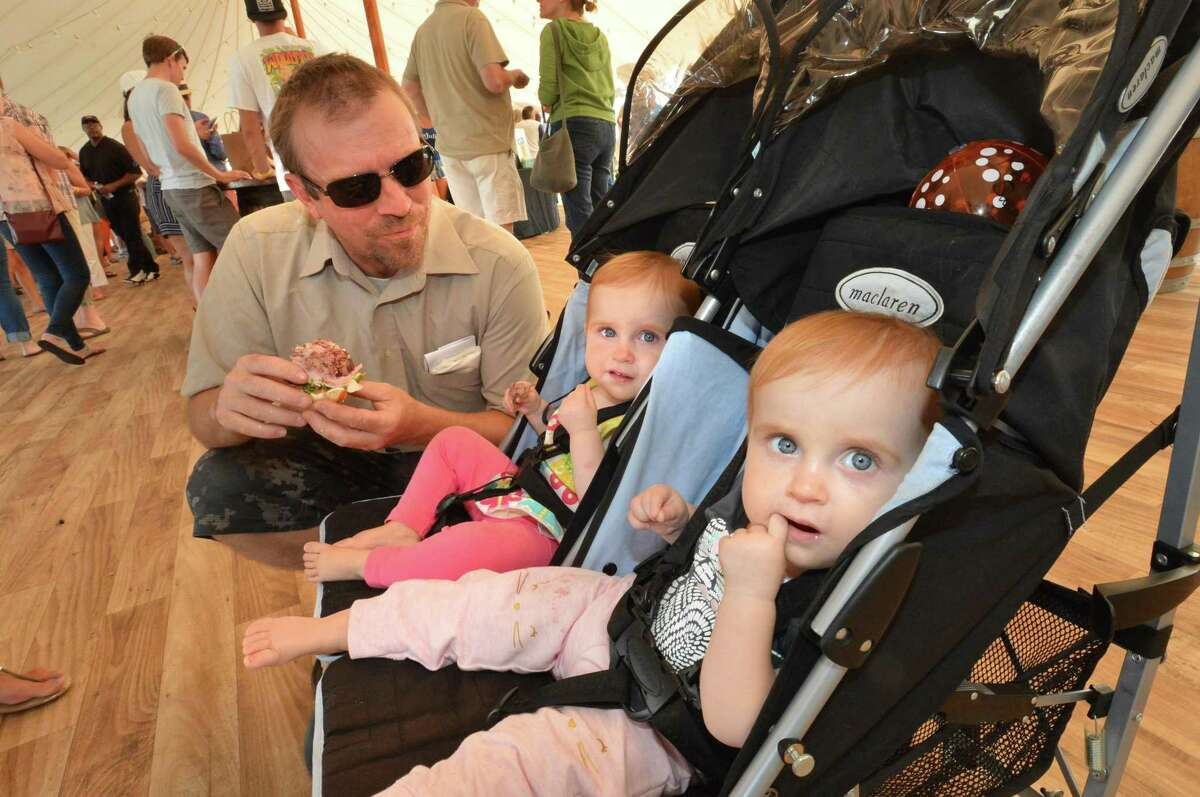 Brian Tyson enjoys a sandwich with his twins 1yr old Evelyn and Rosalynd. at the inaugural Taste of East Norwalk on Sunday, August. 27 2017. People enjoyed a day of food, music, games, and some of East Norwalk's finest local restaurants, food markets, delis and caterers. There was live music and dance performances along with games for kids at the Longshore Pavillion in East Norwalk.