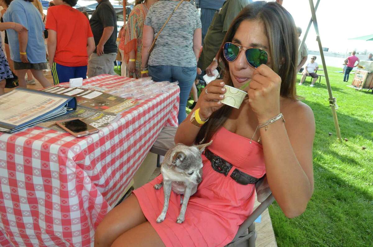 Salina Tavella and Peanut sit and enjoy samples during the inaugural Taste of East Norwalk on Sunday, August 27 2017. People enjoyed a day of food, music, games, and some of East Norwalk's finest local restaurants, food markets, delis and caterers. There was live music and dance performances along with games for kids at the Longshore Pavillion in East Norwalk.