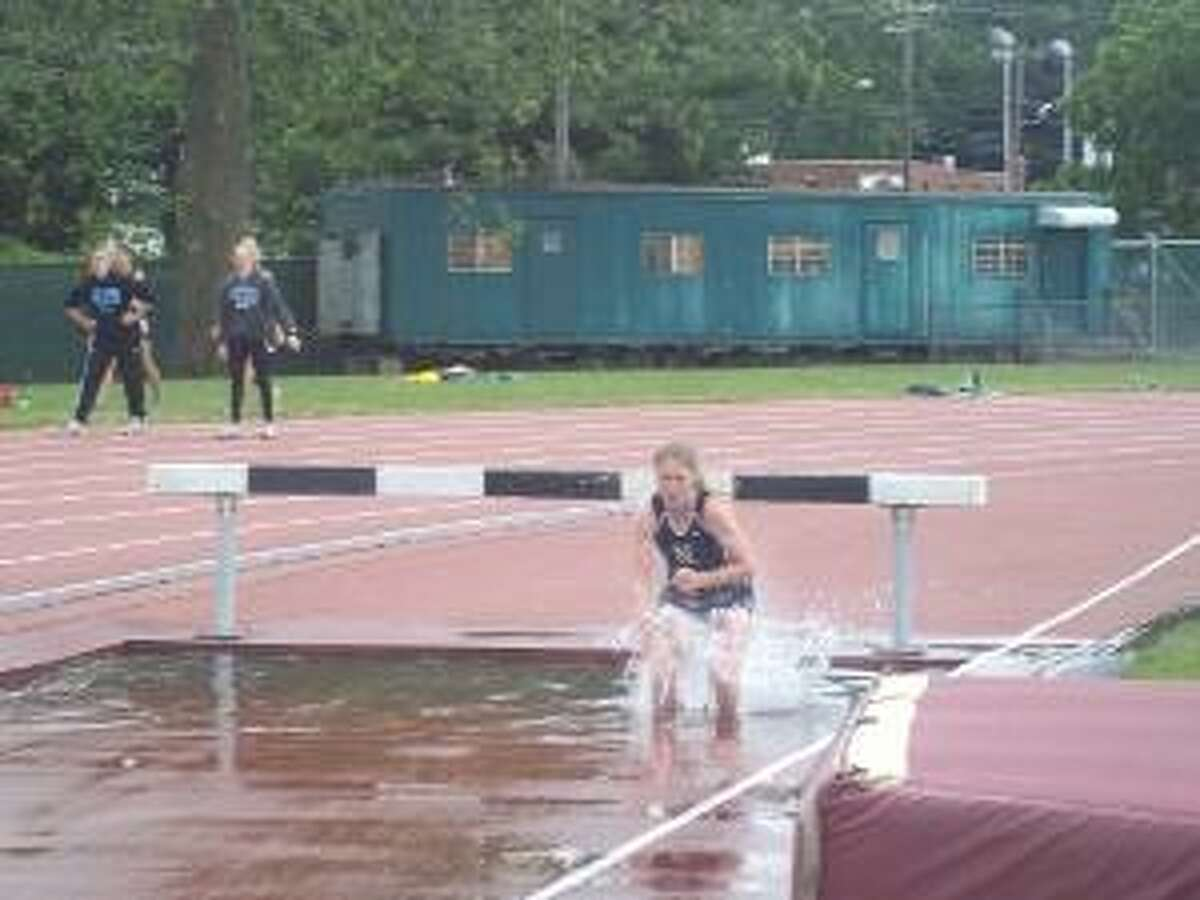 KEVIN D. ROBERTS/Register Citizen Nonnewaug's Jackie Nicholas hits the water after clearing a hurdle during Tuesday afternoon's 2000-meter steeplechase at Willow Brook Park in New Britain. Nicholas captured her third straight state steeplechase title Tuesday.