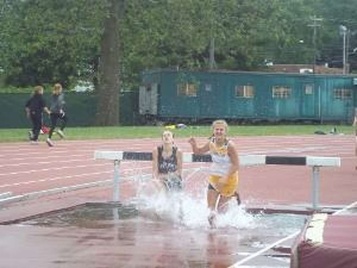 KEVIN D. ROBERTS/Register Citizen Thomaston's Sabrina Olsen and East Lyme's Eva Christensen hit the water after clearing a hurdle during Tuesday afternoon's 2000-meter steeplechase at Willow Brook Park in New Britain. Olsen finished third in the race behind Christensen, who placed second. Nonnewaug's Jackie Nicholas captured her third straight state steeplechase title.