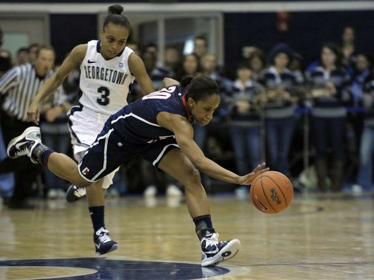 Connecticut's guard Lorin Dixon (30) scrambles for a loose balll near half-court as Georgetown guard Rubylee Wright (3) chases her during the first period of their Big East game in Washington, Saturday, Feb. 26, 2011. (AP Photo/Cliff Owen)