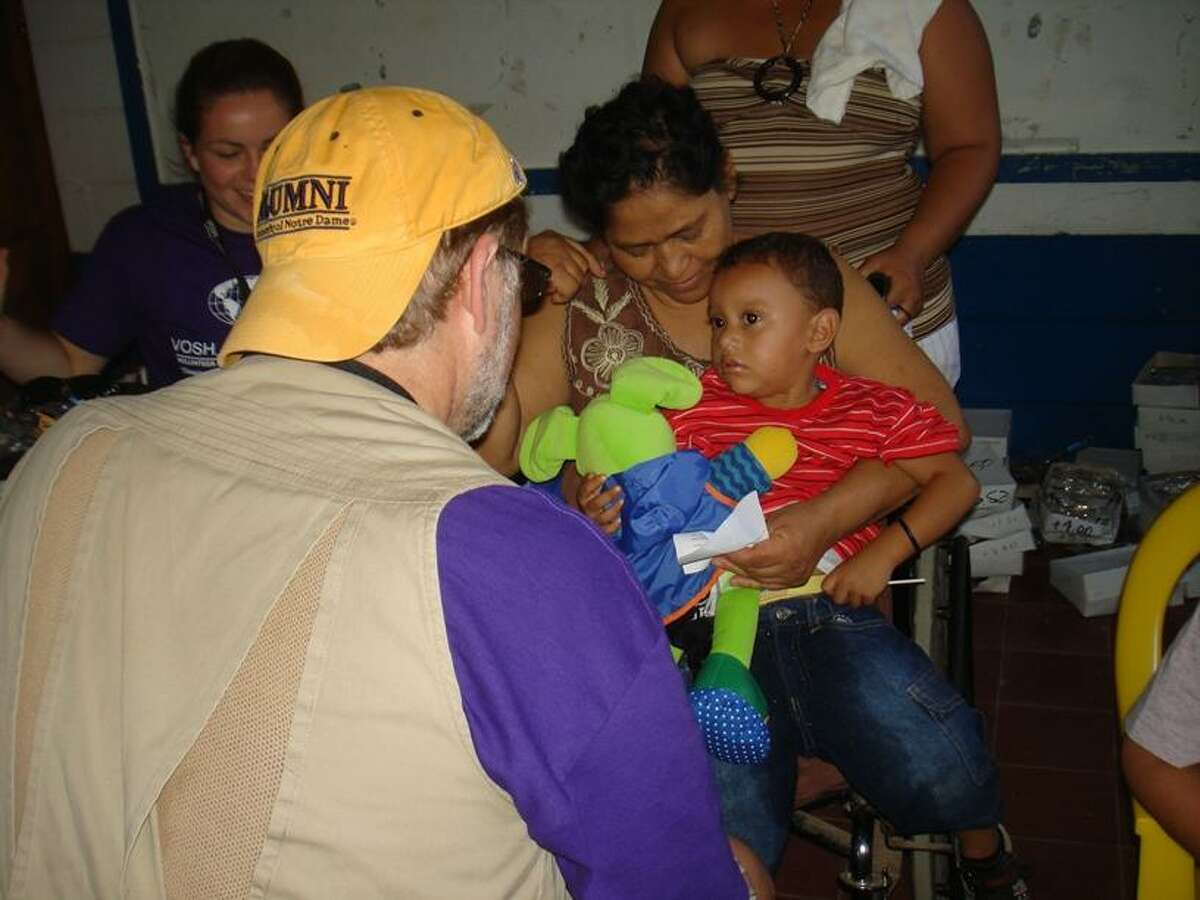 Dr. Matthew Blondin gets acquainted with a young patient at the 14th annual VOSH-CT charitable trip to Nicaragua, where he and other doctors provided a week of free eye care clinics to needy residents.