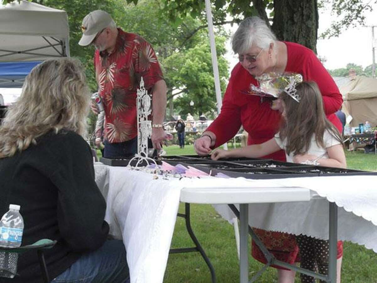 RICKY CAMPBELL/ Register CitizenRiley Storrs, 5, looks at some jewelry Sunday afternoon with her grandmother and grandfater, Debbie and Gary Storrs. The vendor was set up on the green during Winsted's Laurel Festival.