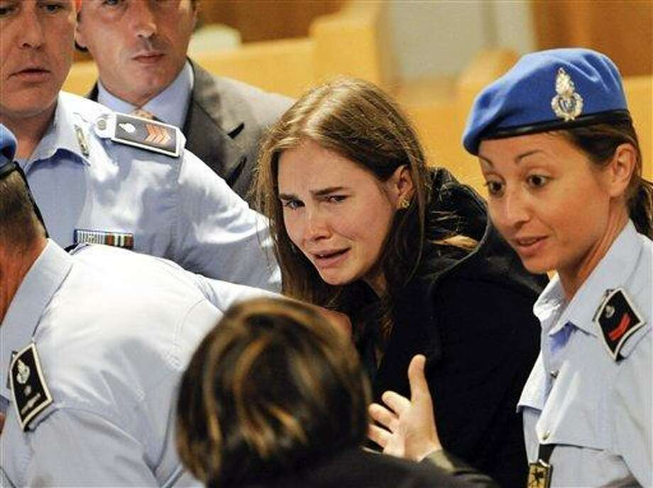 Amanda Knox cries following the verdict that overturns her conviction and acquits her of murdering her British roomate Meredith Kercher, at the Perugia court, Italy, Monday Oct. 3, 2011. An Italian appeals court has thrown out Amanda Knox's murder conviction and ordered the young American freed after nearly four years in prison for the death of her British roommate. Knox collapsed in tears after the verdict was read out Monday. Her co-defendant, Raffaele Sollecito, also was cleared of killing 21-year-old Meredith Kercher in 2007. (AP Photo/Lapresse) ITALY OUT Photo: AP / PRESL