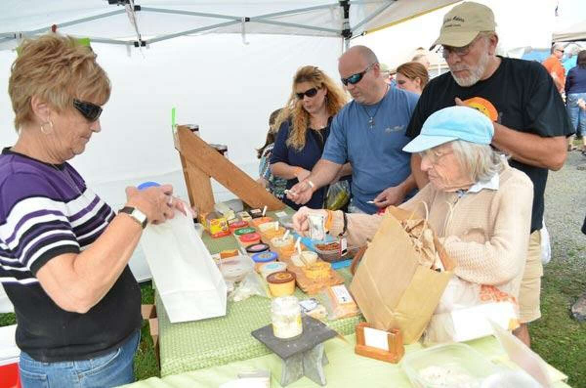 Mary Brockway of Country Pride Cheeses in Hobart, NY faces the long lines of customers sampling and buying her cheese products at the Garlic Festival on Saturday in Bethlehem. Brockway said that they have come to the Garlic Festival for the past five years and they have watched it grow each year. John Berry/Register Citizen