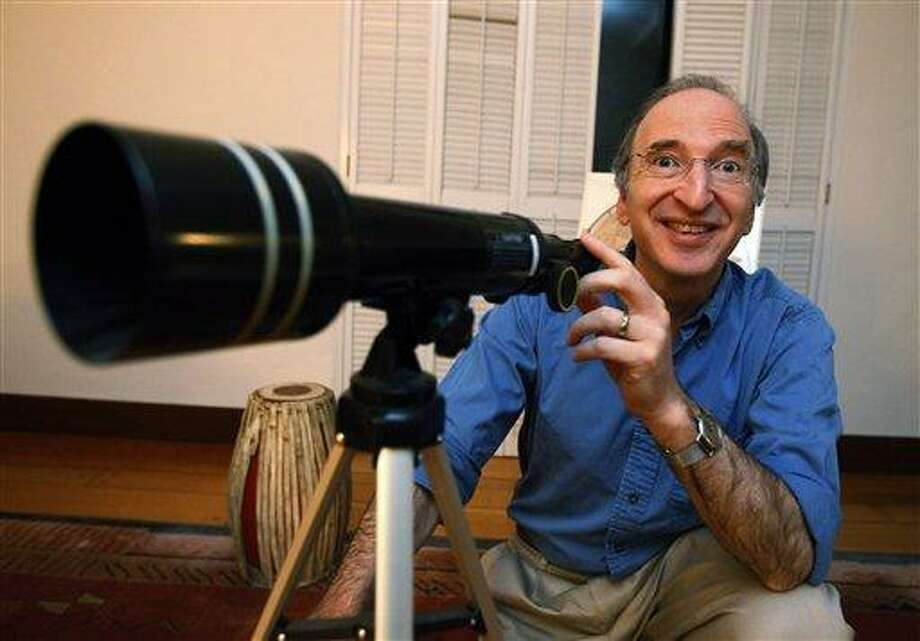 Nobel Prizes winner for physics Saul Perlmutter smiles as he poses with his daughter's telescope at his home in Berkeley, Calif., Tuesday, Oct. 4, 2011 after hearing he had won. The Royal Swedish Academy of Sciences said American Perlmutter would share the 10 million kronor ($1.5 million) award with U.S.-Australian Brian Schmidt and U.S. scientist Adam Riess. Working in two separate research teams during the 1990s, Perlmutter in one and Schmidt and Riess in the other, the scientists raced to map the universe's expansion by analyzing a particular type of supernovas, or exploding stars.  (AP Photo/Paul Sakuma) Photo: AP / AP
