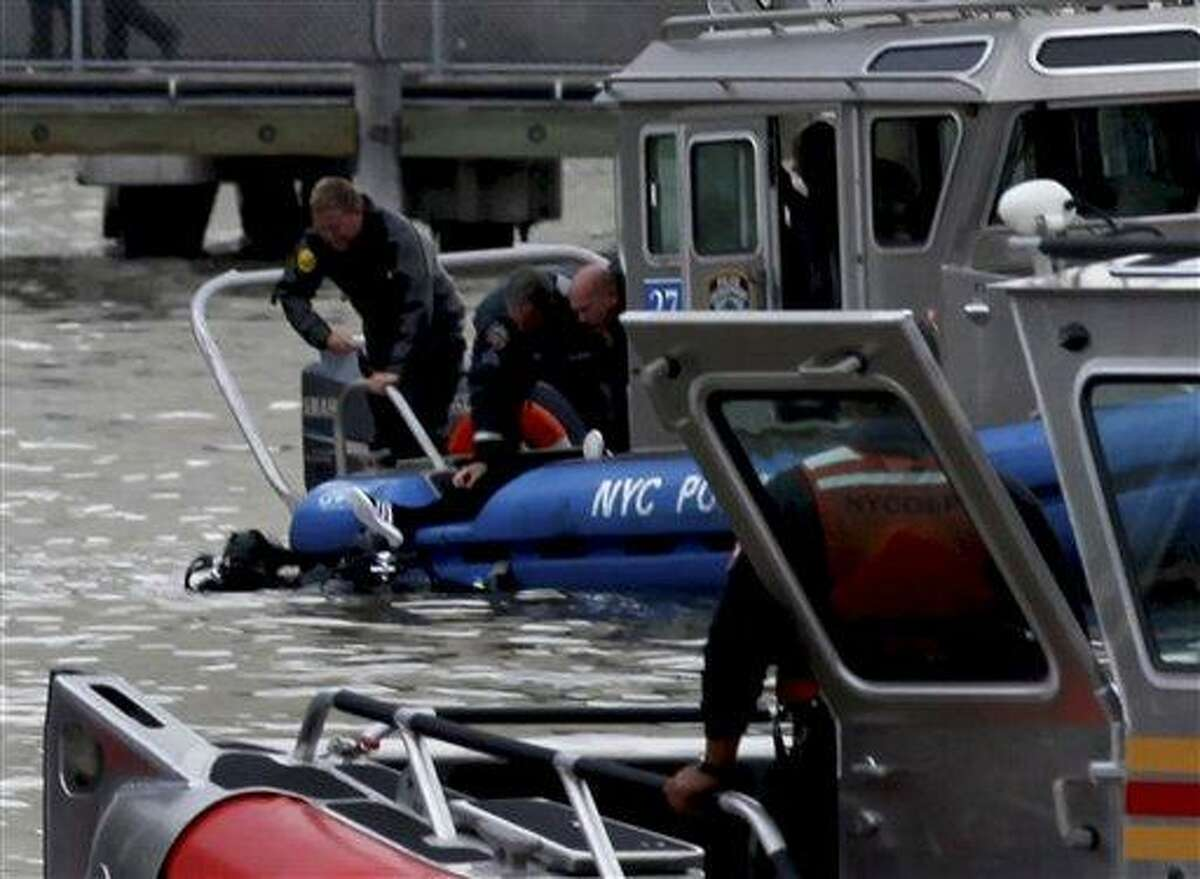 A person is pulled from the East River in New York Tuesday by rescue personal after a helicopter with five people aboard crashed into the river after taking off from a launch pad on the riverbank, killing one and seriously injuring at least two others. (AP Photo/Craig Ruttle)