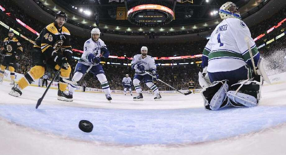 ASSOCIATED PRESS Vancouver Canucks goalie Roberto Luongo (1) looks for the puck as it crosses the goal line for the Bruins' second goal of the first period during Game 6 of the NHL hockey Stanley Cup Finals Monday in Boston. Bruins center David Krejci (46) and Vancouver's Kevin Bieksa (3) and Chris Higgins look on.