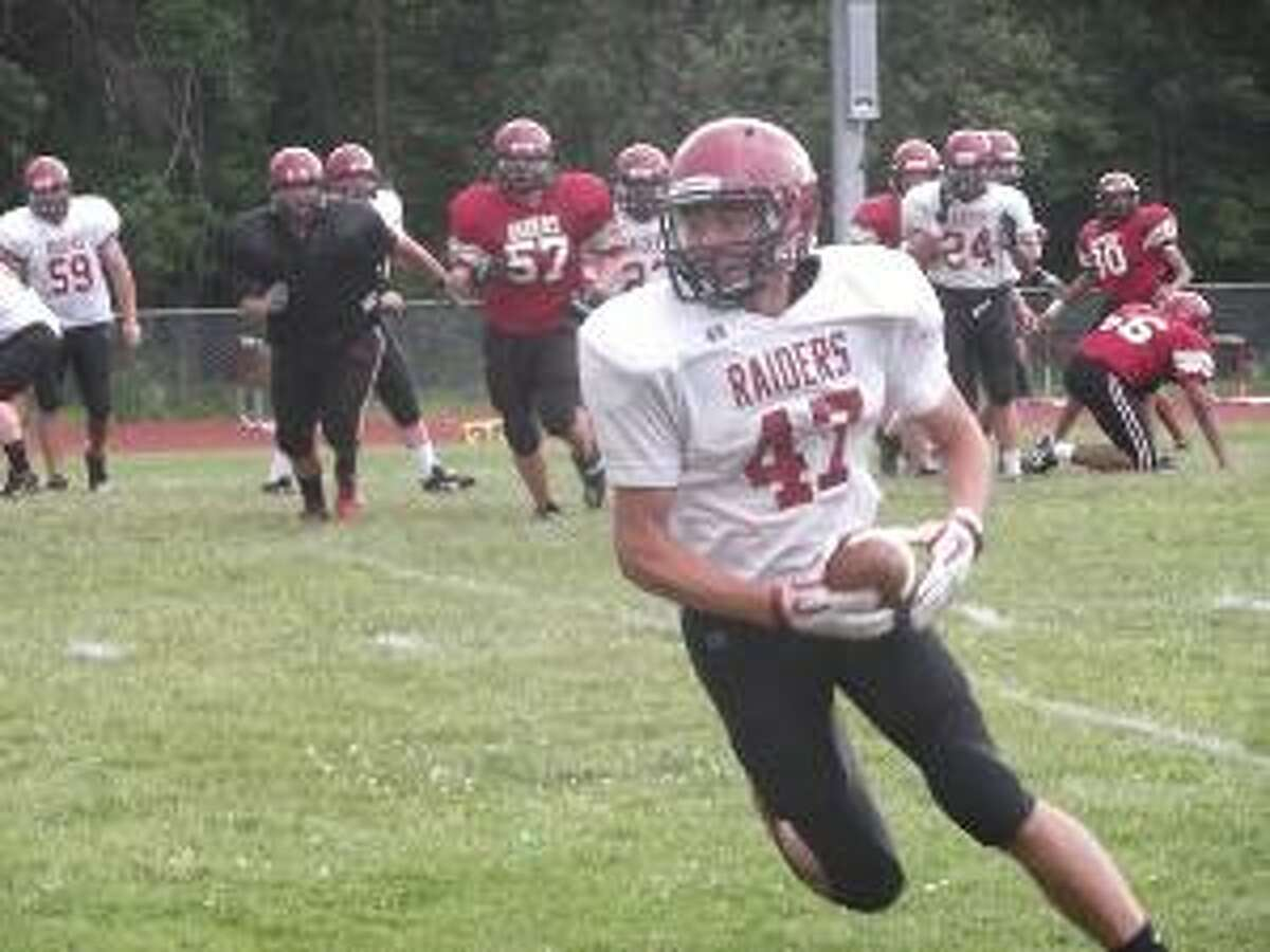 KEVIN D. ROBERTS/Register Citizen Torrington wide receiver Desmond Langs turns upfield after catching a pass during Friday's Red-White scrimmage at Torrington High School. The White team won 30-18. Langs will be a big part of the Red Raider passing game this season. Torrington opens the 2012 season on Friday, Sept. 14 at 7 p.m. against Ansonia at the Robert H. Frost Sports Complex.