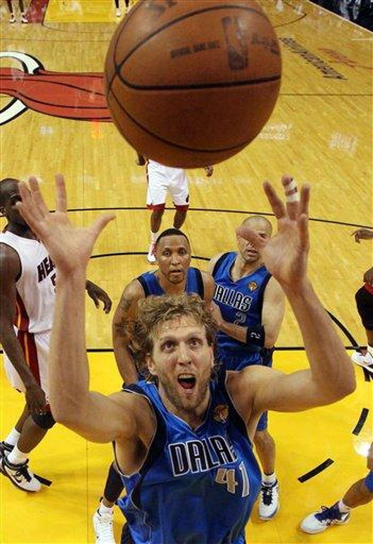 Dallas Mavericks' Dirk Nowitzki goes up for a rebound during the second half of Game 6 of the NBA Finals basketball game against the Miami Heat Sunday in Miami. (AP Photo/Ronald Martinez; Pool)