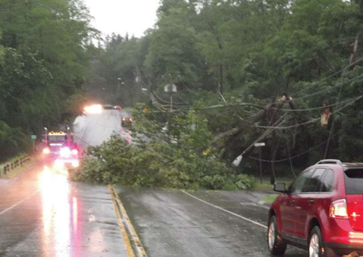 RICKY CAMPBELL/ Register CitizenRoute 118 in Litchfield was closed to traffic Thursday due to a snapped tree which tore down some power lines. Police and CL&P crews were on scene while some drivers waited and others detoured on different routes.
