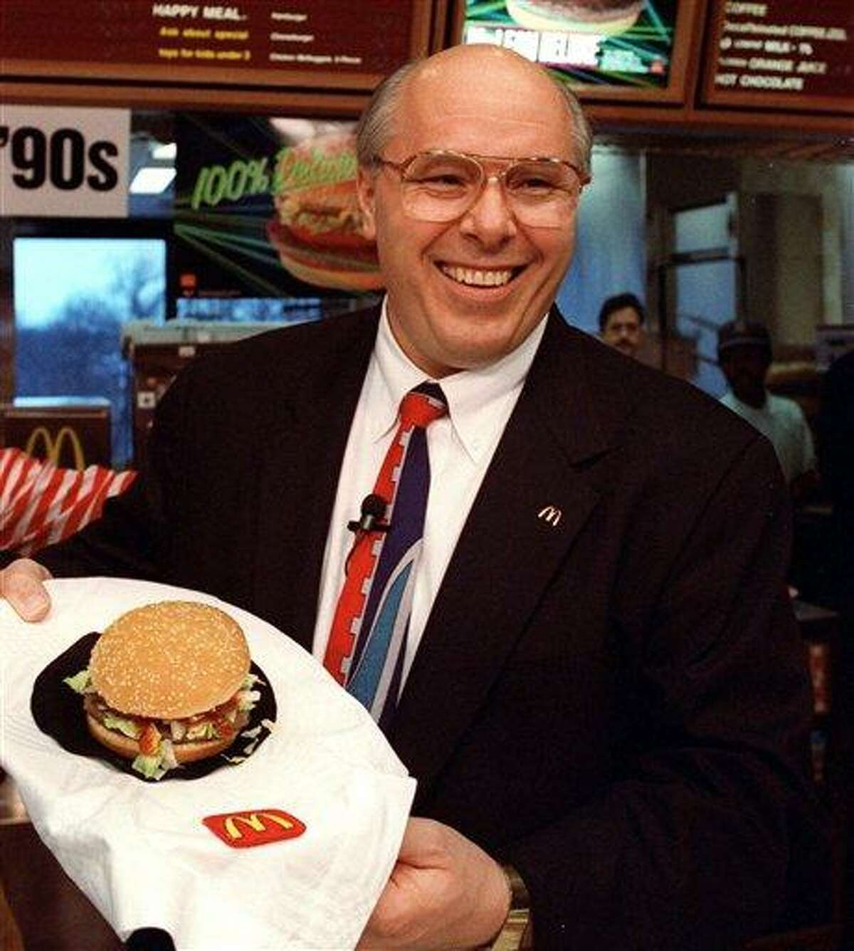 FILE - In this file photo of March 13, 1991, (then) McDonald's Corp. President Ed Rensi shows off the McLean Deluxe Burger during a news conference at the company's Oak Brook, Ill., headquarters. The lower fat hamburger made with seaweed derivative never really caught on with customers. (AP Photo/Ralf-Finn Hestoft, File)