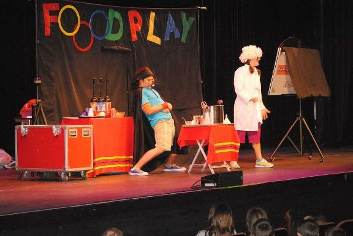 MIKE AGOGLIATI/ Register Citizen Johnny Junkfood, played by Keith Allen and Coach, played by Jenna Hoff, teach kids how soda is made during a presentation of Food play held at the Warner Theatre Monday afternoon. The show teaches kids healthy eating and exercising habits and reached more than 3,200 children in Torrington and Winchester during two shows at the theatre.