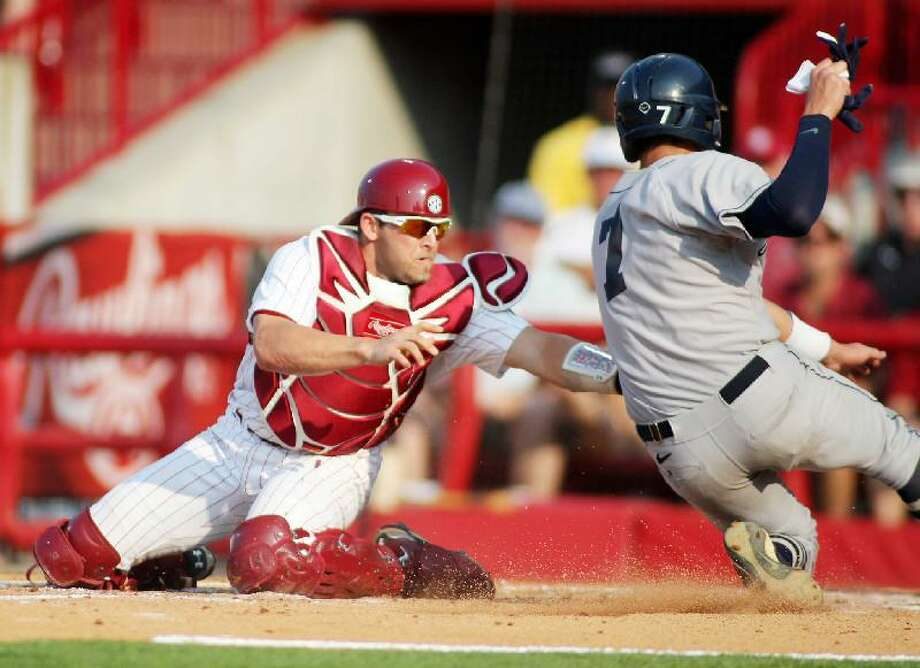 ASSOCIATED PRESS South Carolina catcher Robert Beary (4) puts the tag on Connecticut's Nick Ahmed (7) in the second inning of the first game of a best-of-three NCAA college baseball super regional at Carolina Stadium, Saturday in Columbia, S.C. The Huskies lost 5-1.