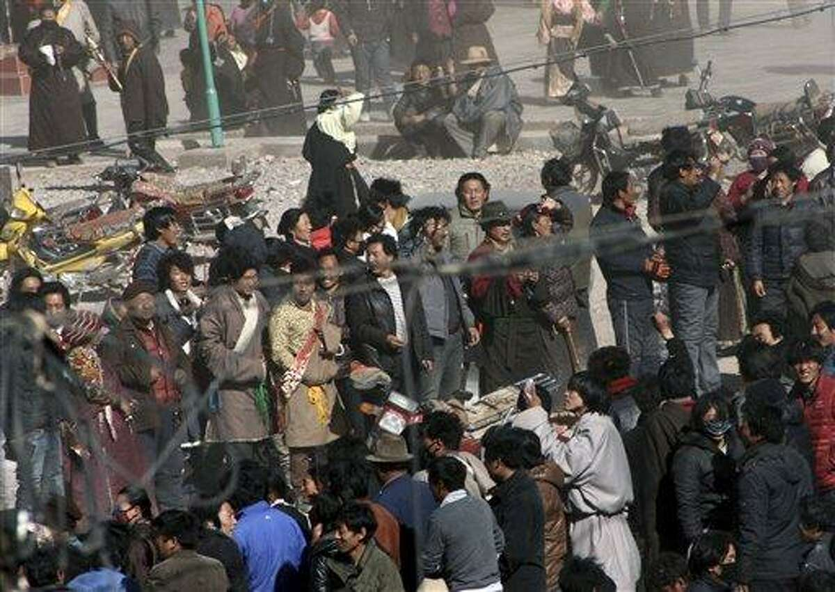 In this photo taken Wednesday, Tibetans gather on the side of a main street in Nangqian county, China's Qinghai province. Another Tibetan has set himself on fire in western China to protest government policies while thousands marched in another part of China to show support for their exiled spiritual leader, the Dalai Lama, a report said. Associated Press