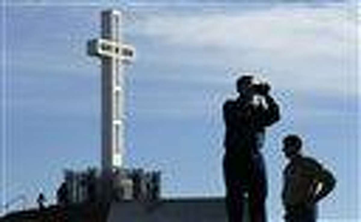 In this 2011 file photo, Rev. John Fredericksen of Orlando, Fla., alongside Burdette Streeter of San Diego, takes a picture in front of the war memorial cross on Mount Soledad in San Diego. Supporters of the war memorial, which is on public land in San Diego, are planning to ask the Supreme Court to reverse a federal court's decision deeming the cross unconstitutional. Associated Press