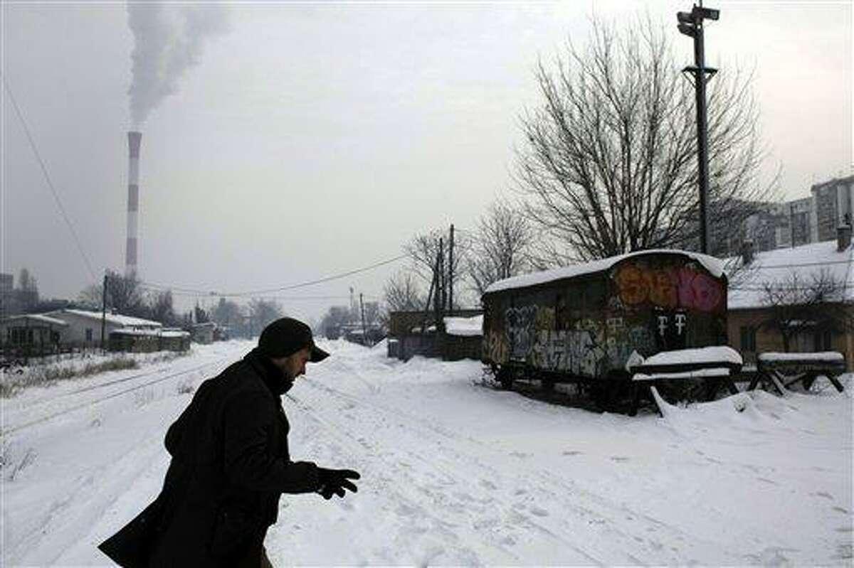 A man races across snow covered train tracks in Belgrade, Serbia, Thursday. Associated Press