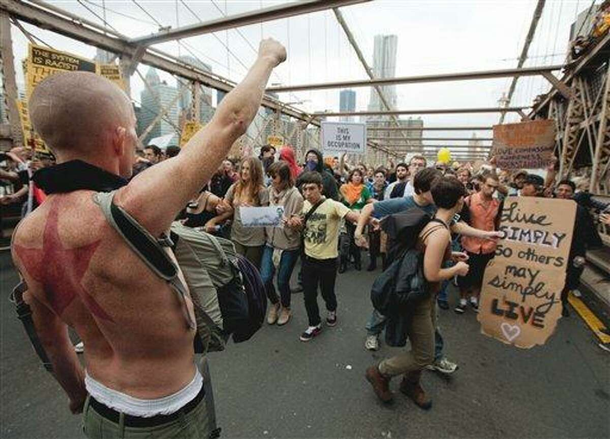 A large group of protesters affiliated with the Occupy Wall Street movement attempt to cross the Brooklyn Bridge, effectively shutting parts of it down Oct. 1 in New York. Police arrested dozens while trying to clear the road and reopen for traffic.(AP Photo/Will Stevens)