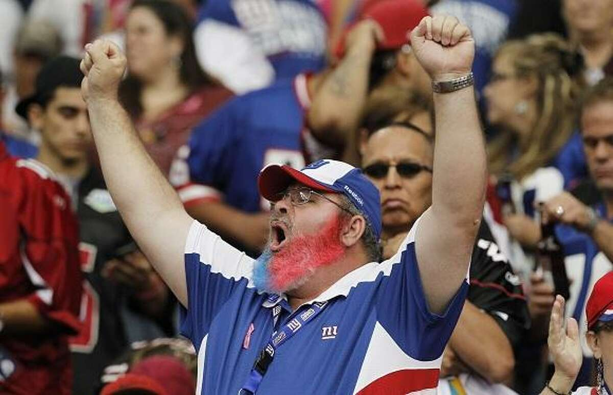A New York Giants fan celebrates a touchdown scored against the Arizona Cardinals during the second quarter in an NFL football game, Sunday, Oct. 2, 2011, in Glendale, Ariz. (AP Photo/Ross D. Franklin)