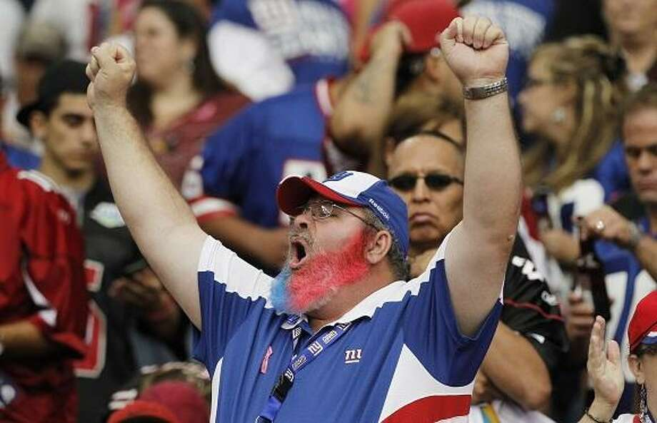 A New York Giants fan celebrates a touchdown scored against the Arizona Cardinals during the second quarter in an NFL football game, Sunday, Oct. 2, 2011, in Glendale, Ariz. (AP Photo/Ross D. Franklin) Photo: ASSOCIATED PRESS / AP2011