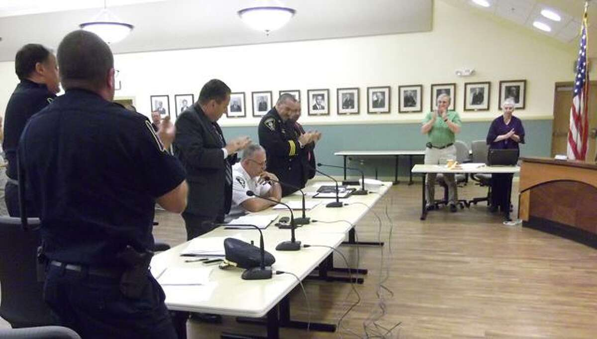 Torrington Fire Chief John Field, seated, receives a standing ovation following his Board of Safety meeting announcement he will retire July 8. (RICKY CAMPBELL / Register Citizen)
