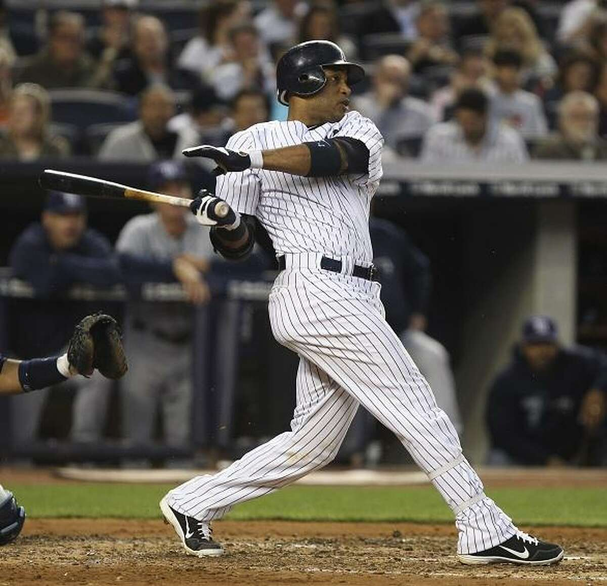 New York Yankees' Robinson Cano follows through on a solo home run during the fourth inning of a baseball game against the Tampa Bay Rays at Yankee Stadium in New York, Wednesday, June 6, 2012. (AP Photo/Seth Wenig)