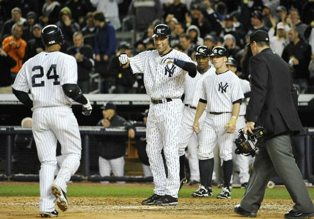 ASSOCIATED PRESS New York Yankees shortstop Derek Jeter, center, greets Robinson Cano at home plate after Cano hit a grand slam off Detroit Tigers relief pitcher Al Alburquerque that scored Jeter, Brett Gardner and Curtis Granderson in the sixth inning during the continuation of Game 1 of their American League division series on Saturday at Yankee Stadium in New York.