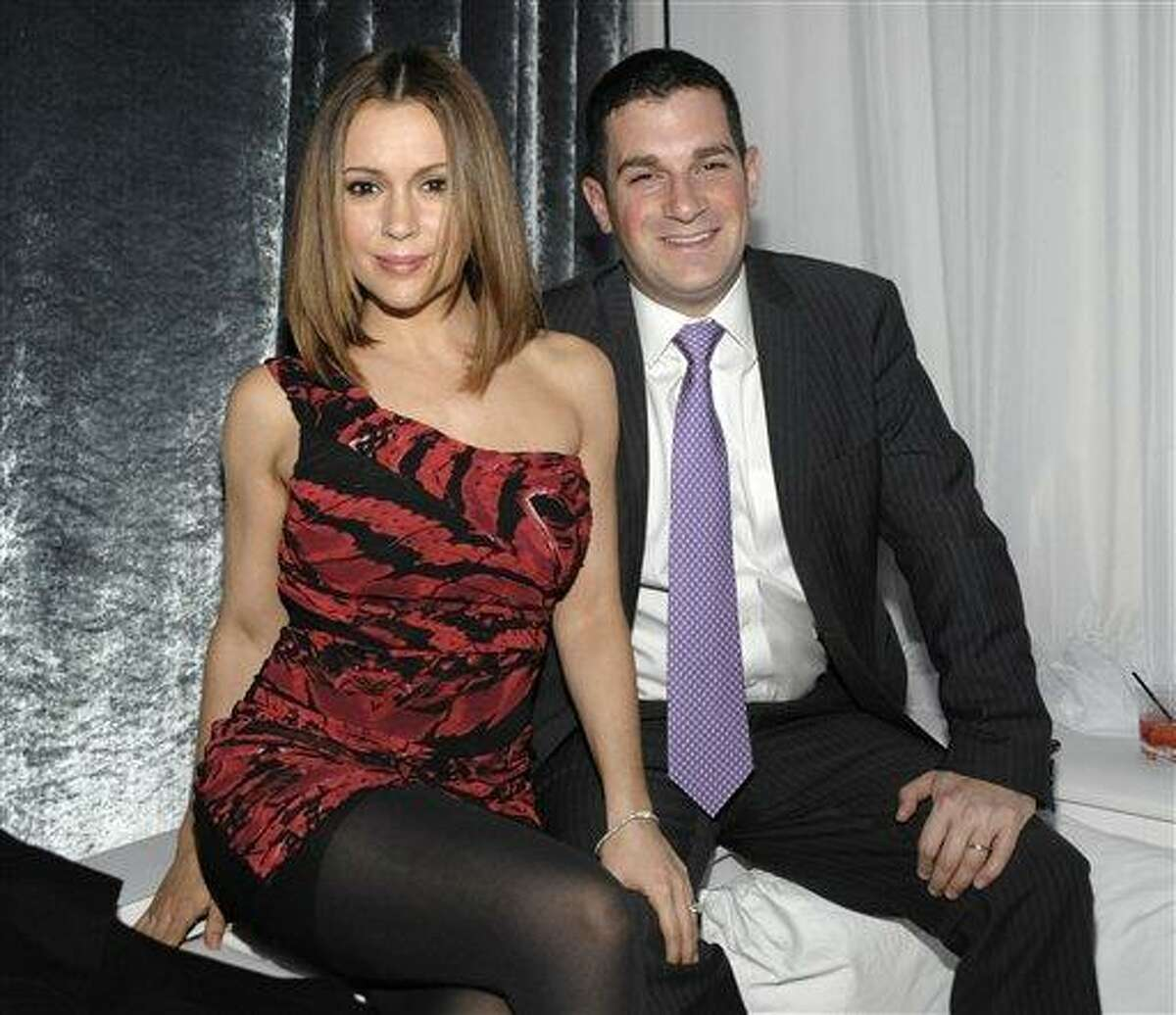 In this Dec. 14, 2010 file photo, actress Alyssa Milano, left, and her husband, David Bugliari appear at the Blu-ray and DVD release party for the animated film