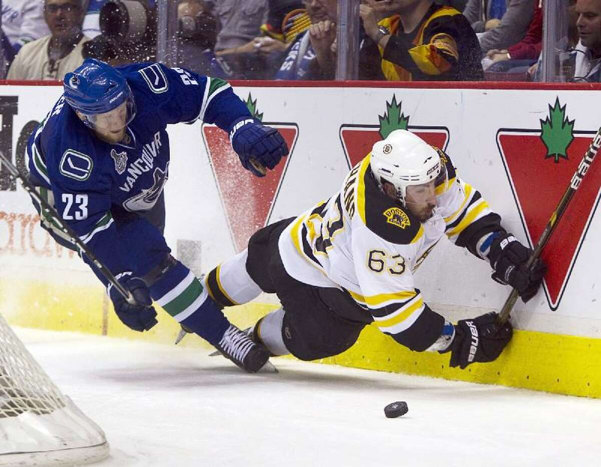 ASSOCIATED PRESS Boston left wing Brad Marchand is checked into the boards by Vancouver defenseman Alexander Edler during the second period of Game 5 of the Stanley Cup finals in Vancouver, British Columbia on Friday. The Canucks won 1-0.