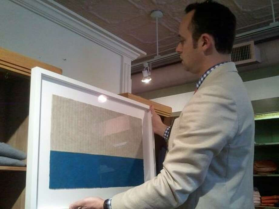 MICHELLE MERLIN/Register Citizen Jonathan Wilson tries to decide where to display local artist Jennifer Ebner's work in R. Derwin Clothiers. Wilson is the organizer of Date Night.