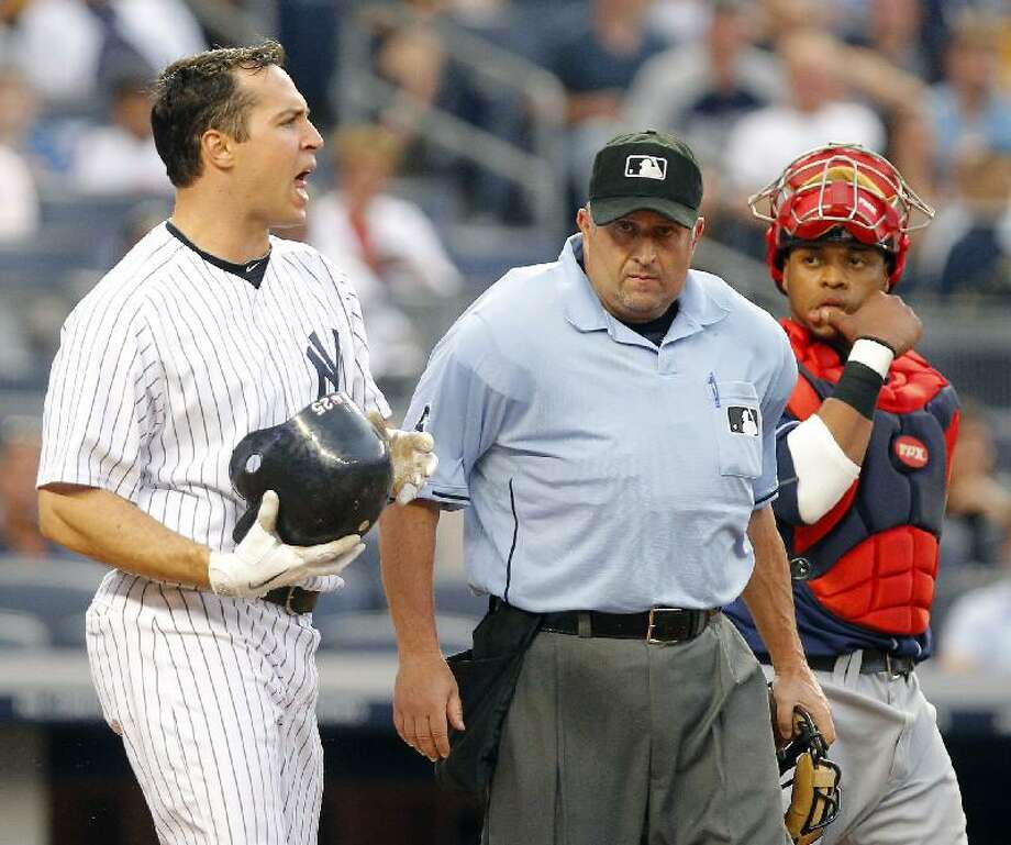 ASSOCIATED PRESS New York's Mark Teixeira, left, shouts at Cleveland Indians pitcher Fausto Carmona after Carmona hit him with a pitch as plate umpire Dale Scott (5) gets in between Teixeira and Indians catcher Carlos Santana, right, in the second inning of Friday's game at Yankee Stadium in New York.