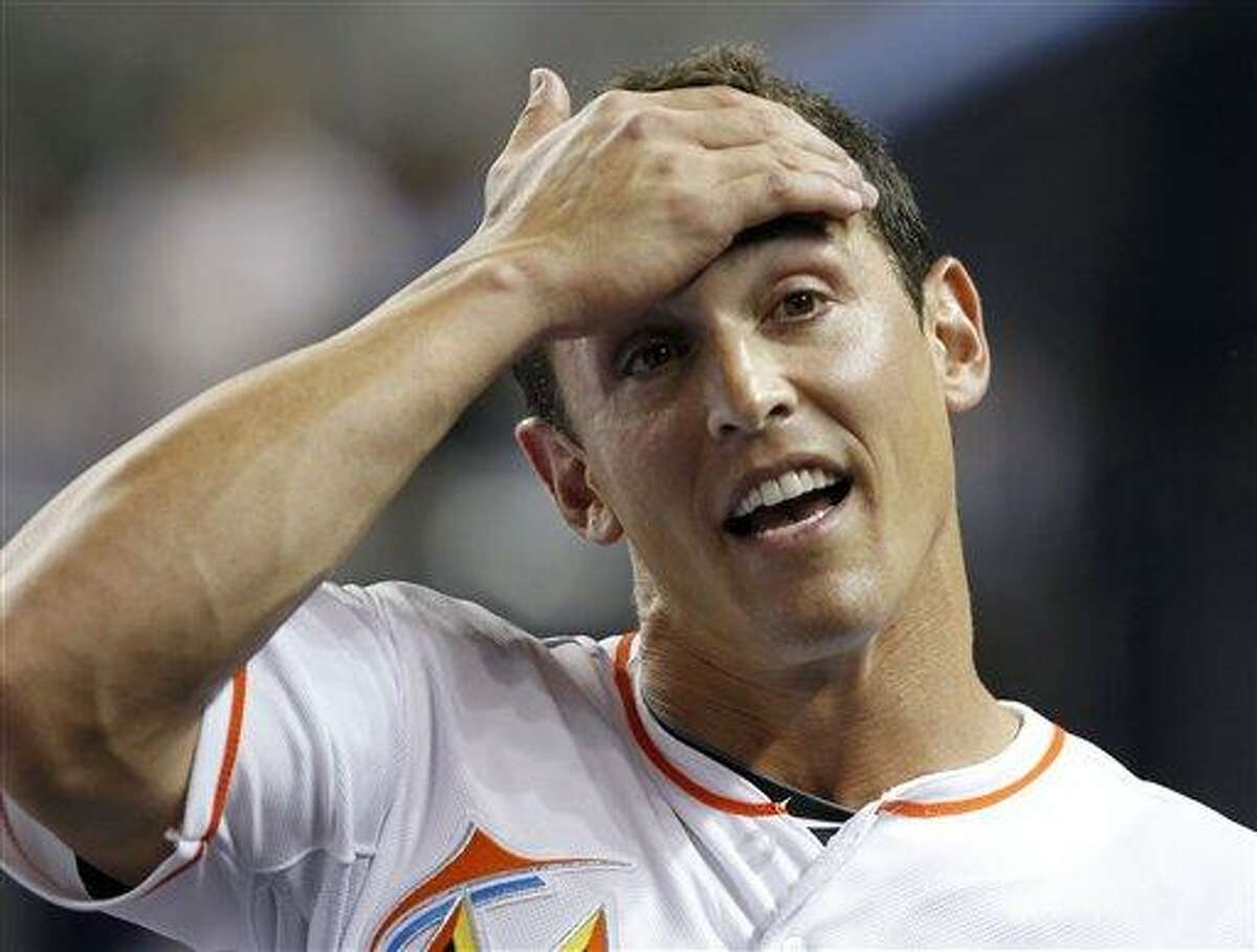 Miami Marlins' Adam Greenberg holds his forehead in the dugout after his at-bat against the New York Mets during the sixth inning of a baseball game in Miami, Tuesday, Oct. 2, 2012. (AP Photo/Alan Diaz)