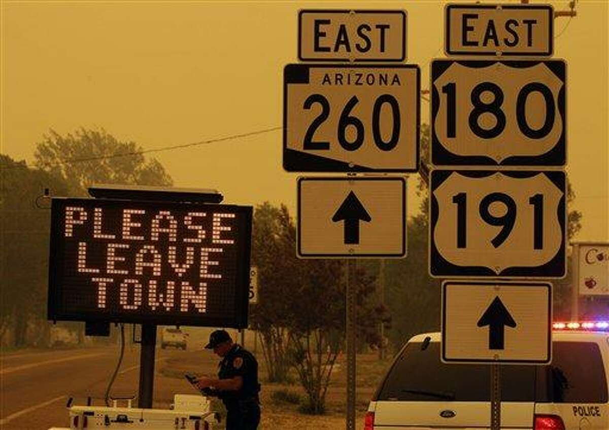 A sign asks for residents to evacuate as the Wallow Fire approaches in Springerville, Ariz., Wednesday, June 8, 2011. A raging forest fire in eastern Arizona has scorched an area the size of Phoenix, threatening thousands of residents and emptying towns as the flames raced toward New Mexico.(AP Photo/Marcio Jose Sanchez)