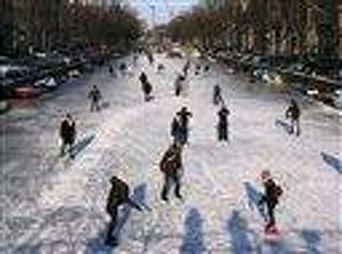 People skate on the frozen Keizersgracht canal in Amsterdam, Netherlands, Tuesday, as volunteers poured onto frozen rivers and lakes in the northern Netherlands to shovel away snow that is one of the major hurdles in the way of a grueling speedskating race called Elfstedentocht, or 11 Cities Tour being held for the first time in 15 years. Associated Press