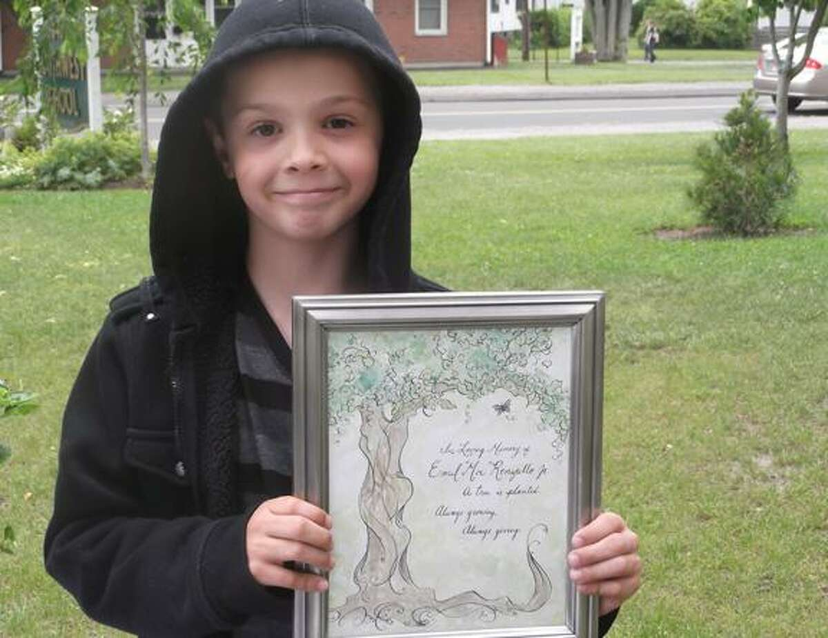 Southwest School second grader Remi DeSmith holds up a plaque dedicating an evergreen outside the school to Emil
