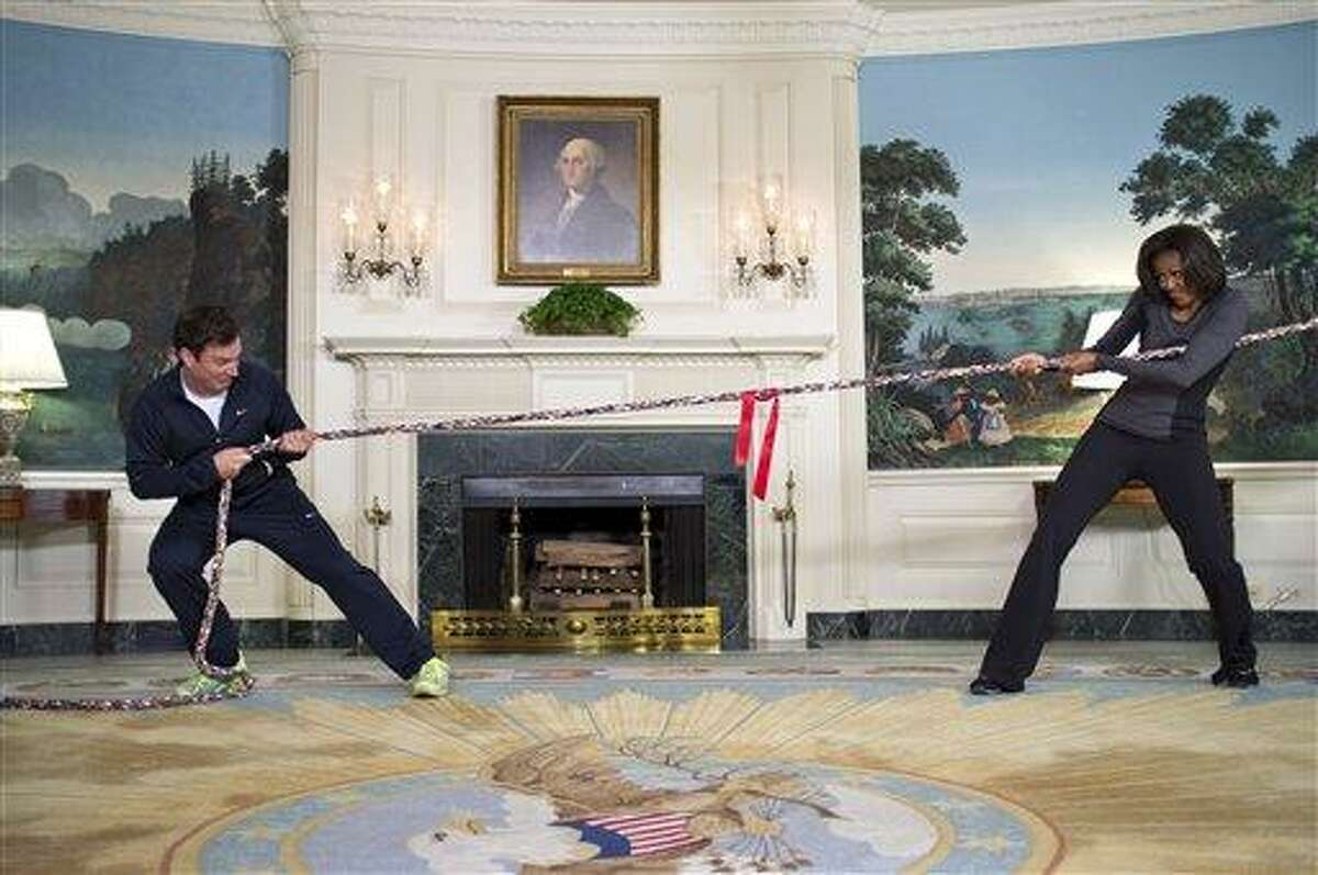 In this image released by The White House, first lady Michelle Obama participates in a tug of war with television host Jimmy Fallon in the Blue Room of the White House during a taping of