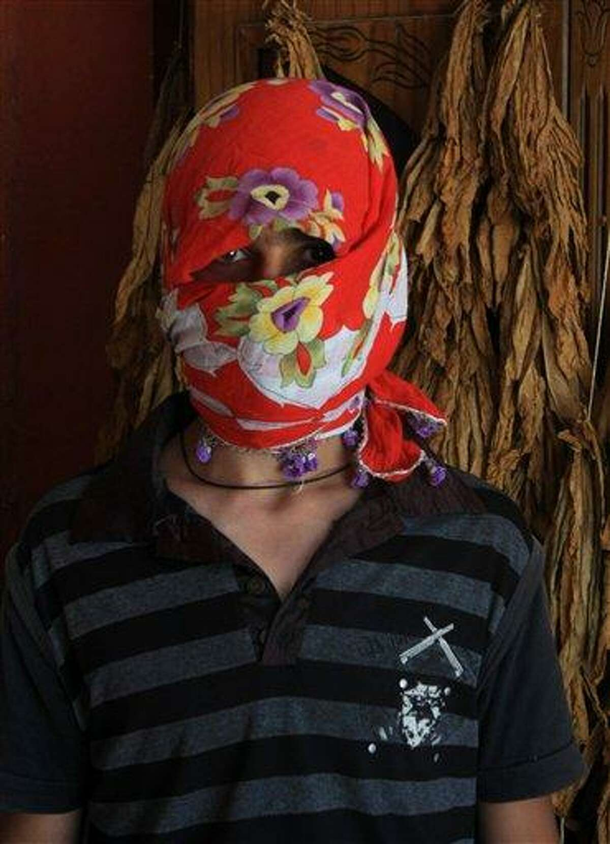 A Syrian boy who crossed the Syria-Turkey border Wednesday covers his face while he speaks to journalists in the Turkish village of Guvecci in Hatay province, Turkey, Thursday, June 9, 2011. Turkey said Wednesday it would open the border to Syrians fleeing violence.(AP Photo/Selcan Hacaoglu)