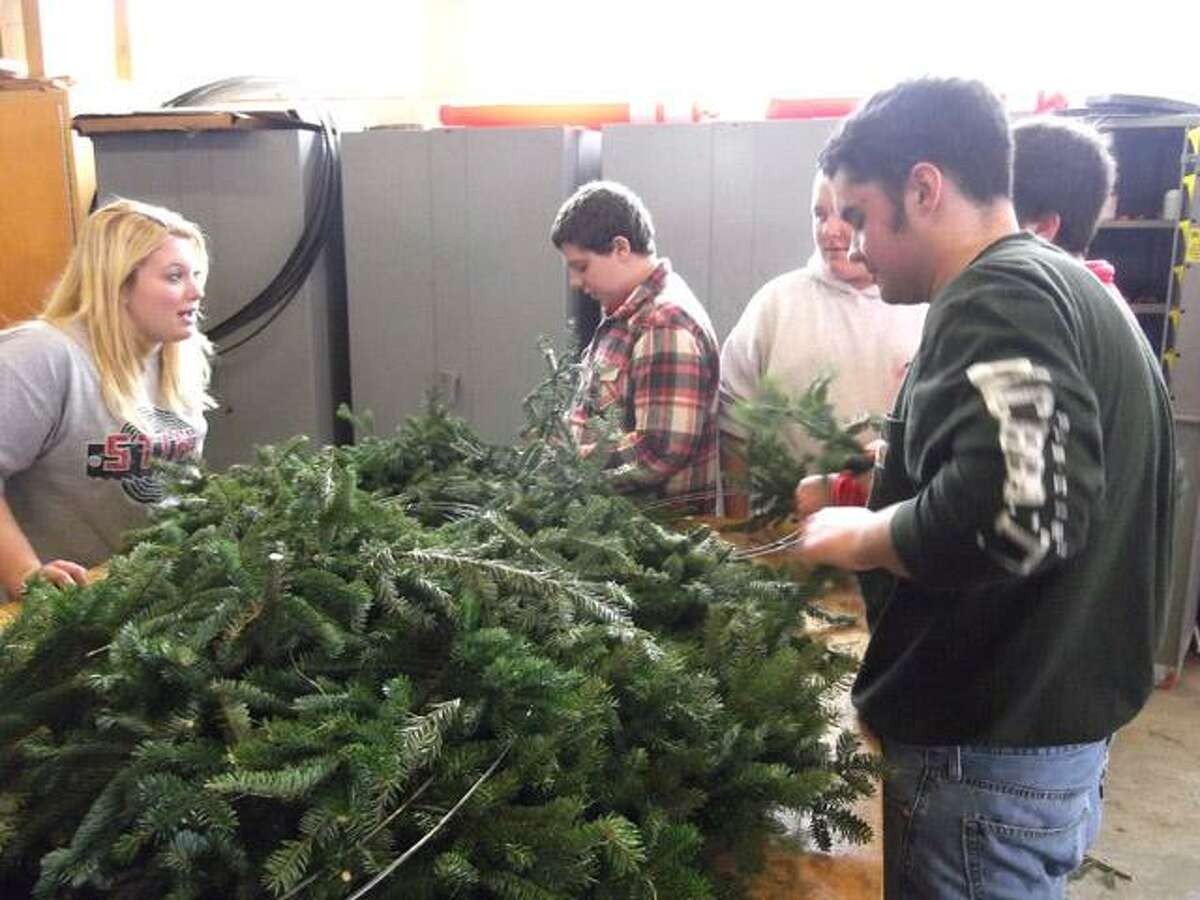 RICKY CAMPBELL/ Register Citizen Sophomores at Wamogo Regional High School continued creating holiday wreaths Tuesday for the school's FFA annual holiday sale, which includes trees, centerpieces, swags and amaryllis and narcissi.