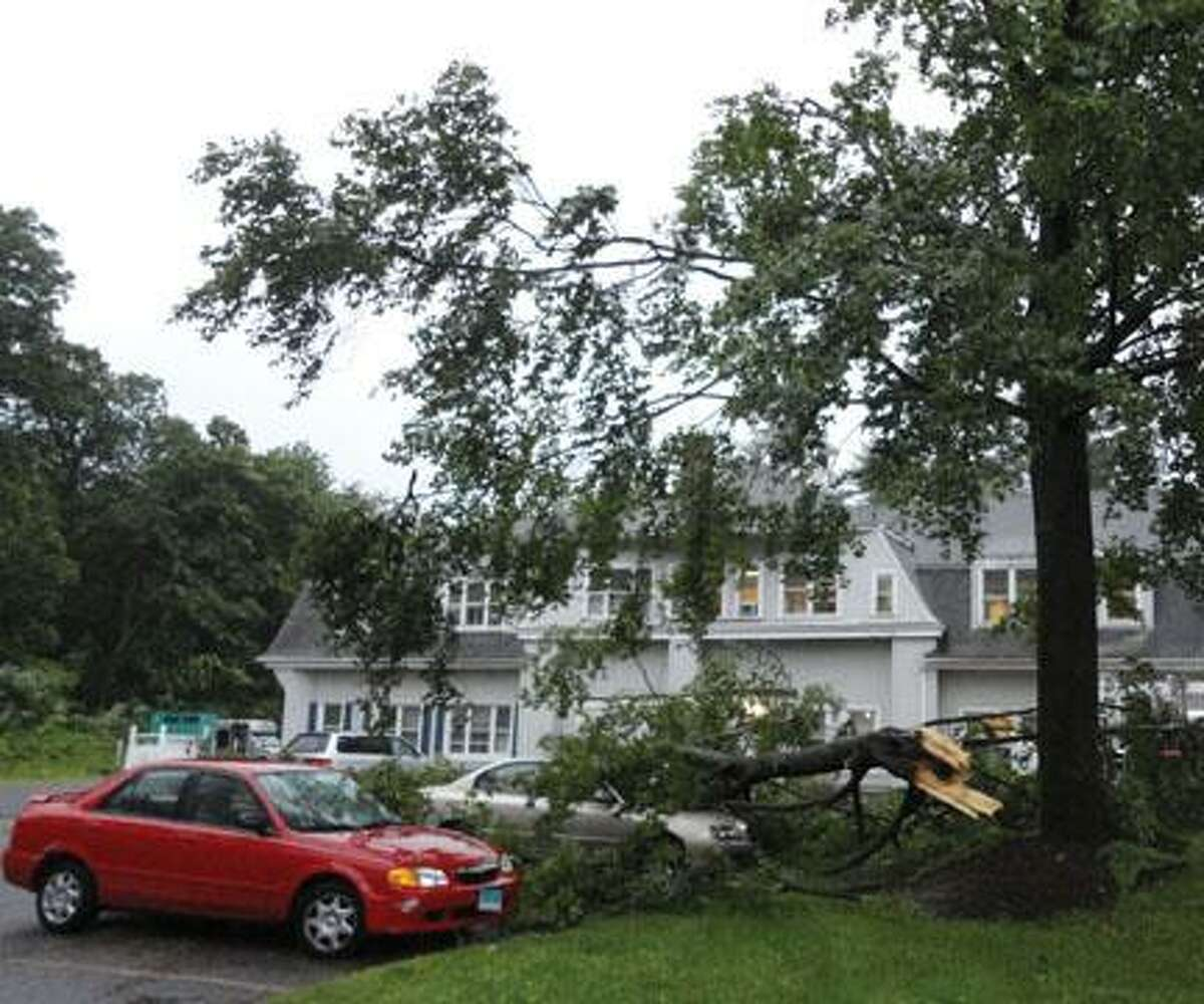 JASON SIEDZIK / Register CitizenOne car sits as victim to a storm-damaged tree on the grounds of Wolcott Hall Nursing Home and Rehabilitation Center in Torrington. Storms knocked down trees and power lines across Connecticut Thursday afternoon.