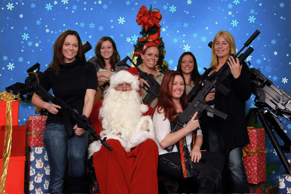 This undated photo provided by the Scottsdale Gun Club shows people posing with Santa Claus and several automatic weapons at the Scottsdale, Ariz. club. Ron Kennedy, general manager of the gun club, says the business got the idea for the photo op last year when a club member happened to come in dressed as Santa and other members wanted their picture taken while they were holding their guns. He says people have used the photos for Christmas cards and Facebook posts. (AP Photo/Scottsdale Gun Club, Gordon Murray)