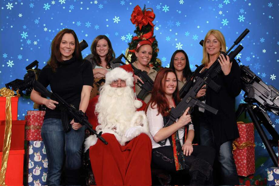 This undated photo provided by the Scottsdale Gun Club shows people posing with Santa Claus and several automatic weapons at the Scottsdale, Ariz. club. Ron Kennedy, general manager of the gun club, says the business got the idea for the photo op last year when a club member happened to come in dressed as Santa and other members wanted their picture taken while they were holding their guns. He says people have used the photos for Christmas cards and Facebook posts. (AP Photo/Scottsdale Gun Club, Gordon Murray) Photo: ASSOCIATED PRESS / AP2011