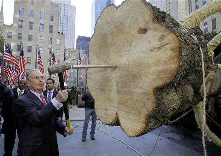 New York Mayor Michael Bloomberg takes his turn to drive the spike in the bottom of the annual Rockefeller Center Christmas tree, in New York, Friday, Nov. 11, 2011. The 74-foot Norway Spruce, from Mifflinville, Pa., is approximately 75 years old and is scheduled to be illuminated Nov. 30. (AP Photo/Richard Drew) Photo: AP / AP