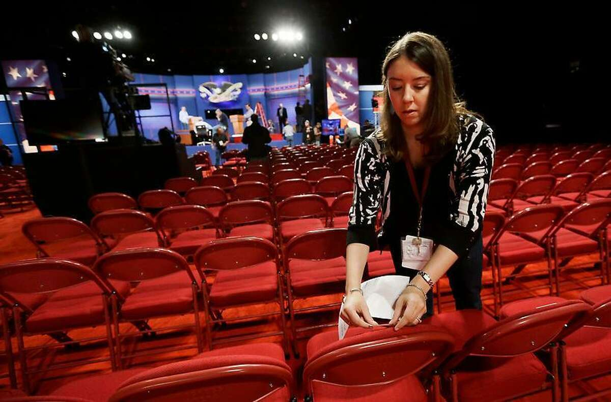 A worker labels chairs in the Magness Arena, site of tonight's presidential debate, on the campus of the University of Denver. Associated Press