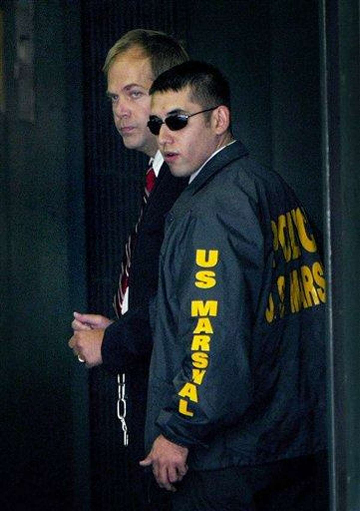 In this Sept. 2, 2003, file photo, John Hinckley, left, who shot President Ronald Reagan in 1981, arrives at Federal Court in Washington guarded by U.S. Marshals. Associated Press