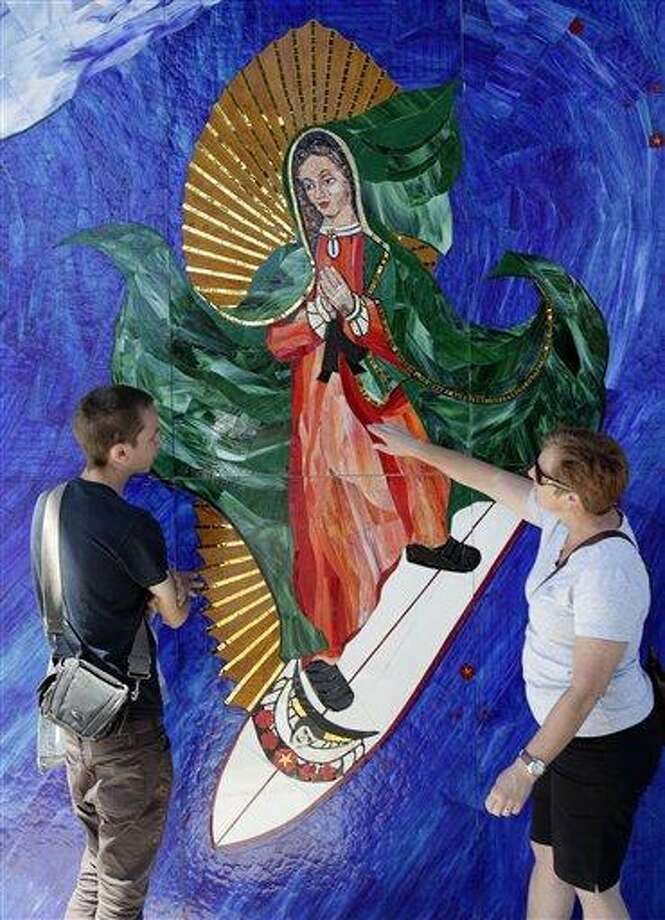 In this May 27, 2011 photo, Anthea Beletsis, right, of Encinitas, Calif.,  and Jules Itzkoff, of Cincinatti, Ohio, look at an image of the Virgin of Guadalupe riding a surfboard that hangs under a train bridge in Encinitas, Calif. The unauthorized artwork is drawing a mass following, and even city officials who say she must go say they too have been taken by her. (AP Photo/Gregory Bull) Photo: ASSOCIATED PRESS / AP2011