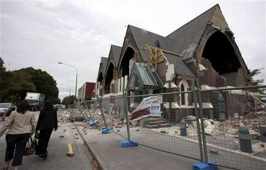 People walk past a church in Christchurch, New Zealand, which was destroyed after an earthquake struck Tuesday, Feb. 22, 2011. The 6.3-magnitude quake collapsed buildings and is sending rescuers scrambling to help trapped people amid reports of multiple deaths. (AP Photo/NZPA, Pam Johnson) NEW ZEALAND OUT, NO ARCHIVES, NO SALES Photo: AP / NZPA