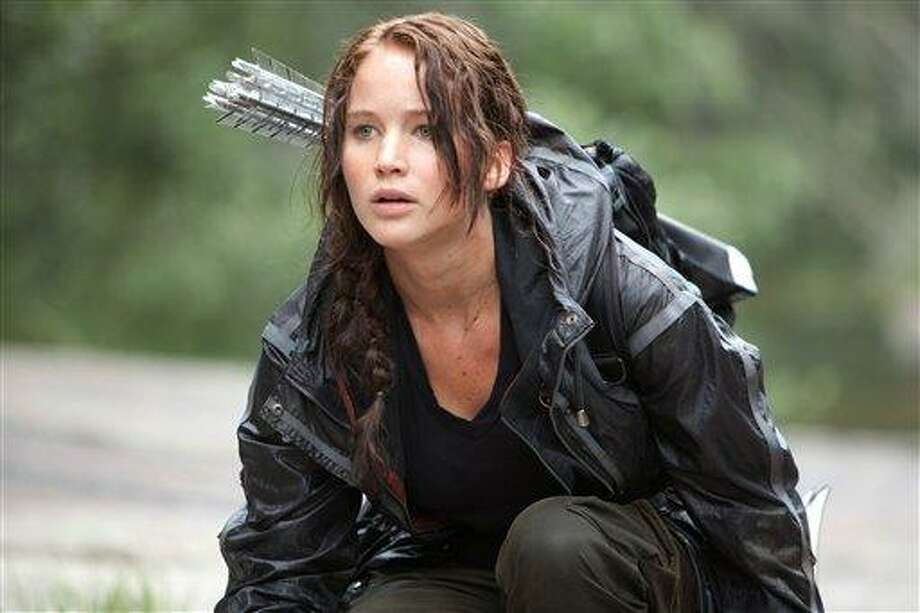"In this image provided by Lionsgate, Jennifer Lawrence portrays Katniss Everdeen in a scene from ""The Hunger Games.""  ""Bridesmaids"" and ""The Hunger Games"" are battling for the most buckets of golden popcorn at the MTV Movie Awards. The raunchy comedy and survival saga are the top nominees at Sunday's 21st annual extravaganza with eight nods apiece. Photo: AP / AP2011"