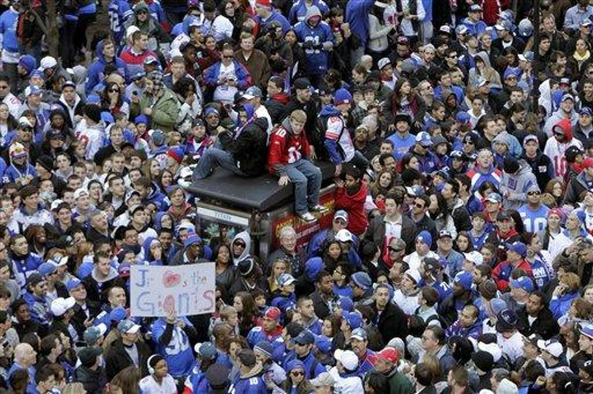 Fans line the streets in lower Manhattan waiting for the start of the New York Giants Super Bowl parade in New York Tuesday. Associated Press