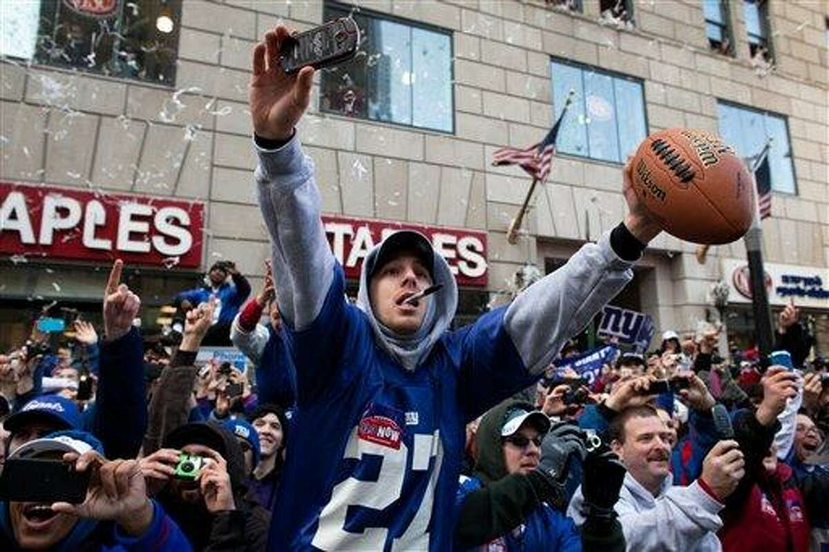 New York Giants fans cheer and reach for autographs from the players during the team's NFL football Super Bowl parade in New York Tuesday. Associated Press